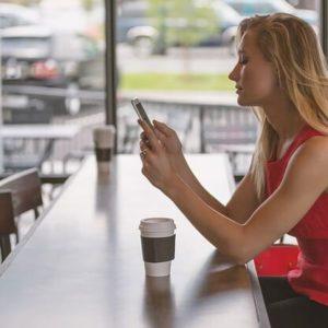 友達と待ち合わせをしている隙間時間にアプリで英語学習をしている女性